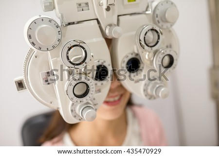 Woman looking through phoropter during eye exam - stock photo
