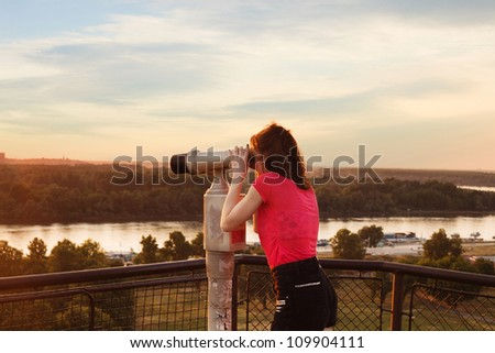 woman looking through sightseeing  binoculars on Belgrade Fortress sky, river and city in background - stock photo