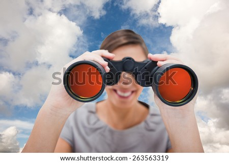 Woman looking through spyglasses against blue sky with white clouds - stock photo