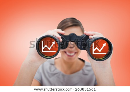 Woman looking through spyglasses against orange - stock photo