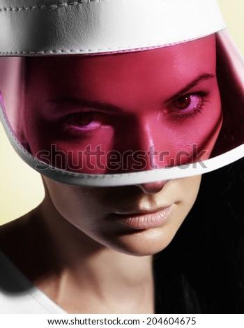 woman looking through the pink sun visor at camera  - stock photo
