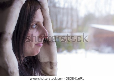 Woman looking through the window the cold winter wrapped with a fur coat