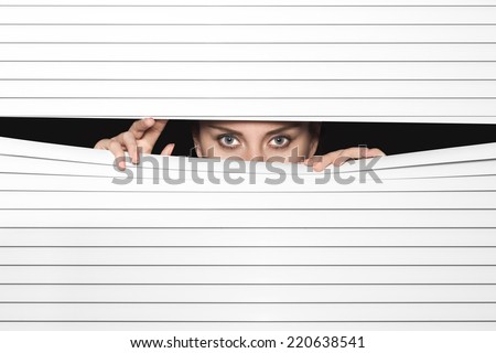 Woman Looking Through Venetian Blinds - stock photo