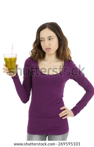 Woman looking to her glass of green smoothie with a bitter face - stock photo