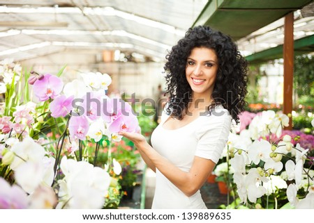 Woman looking to orchids in a greenhouse - stock photo