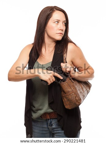 Woman looking to the side and carrying a Concealed Gun in her Purse | Attractive female shooter holding weapon against white background. - stock photo