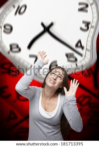 Woman looking up and trying to stop a big warped clock above her with a red background made of warped clocks - stock photo