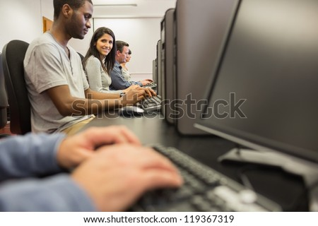 Woman looking up from computer class in college - stock photo