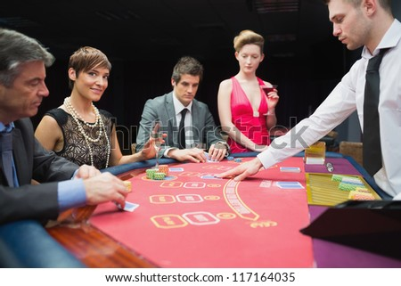 Woman looking up from poker game and smiling in casino - stock photo