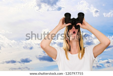 woman looking up using binoculars against a cloudy sky background - stock photo