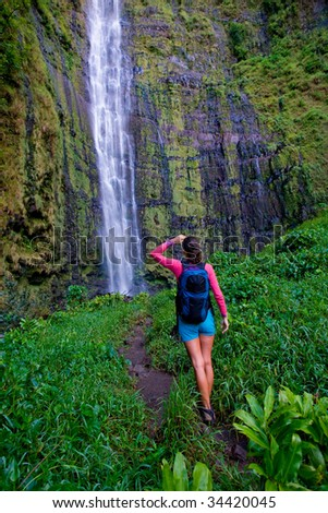 woman looks at amazing waterfall after long hike - stock photo