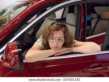 woman looks in a car mirror - stock photo