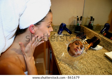 Woman looks in Mirror - stock photo