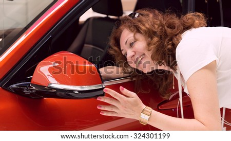 woman looks in mirror of red car - stock photo