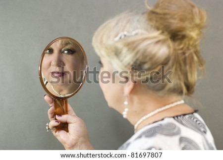 woman looks in the mirror - stock photo