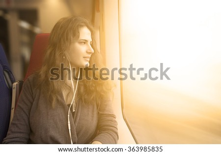 woman looks out window while sitting in the train. - stock photo