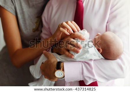Woman looks over man's shoulder on the little baby lying on his arms - stock photo