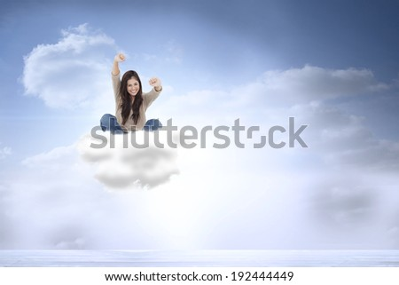 Woman looks straight ahead as she celebrates in front of her laptop against beautiful blue sky with clouds - stock photo