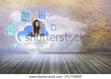 Woman looks straight ahead as she celebrates in front of her laptop against clouds in a room - stock photo