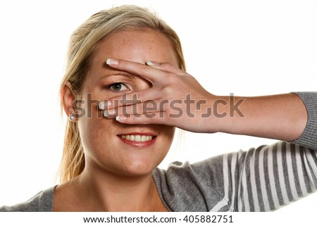 woman looks through fingers of her hand - stock photo
