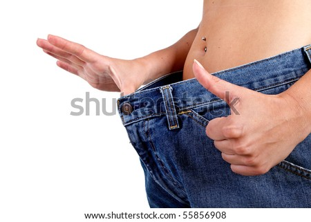 Woman loosing weight and giving a thumb up sign to her new waistline. - stock photo