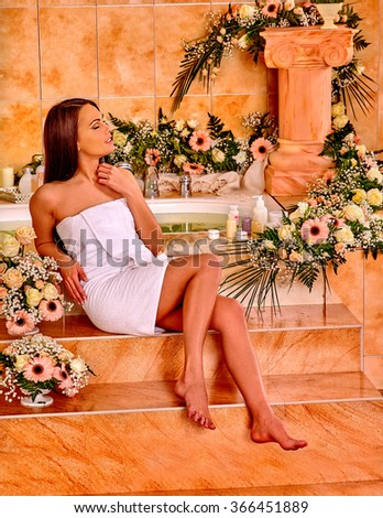 Woman luxuriate at flowers water spa.  - stock photo