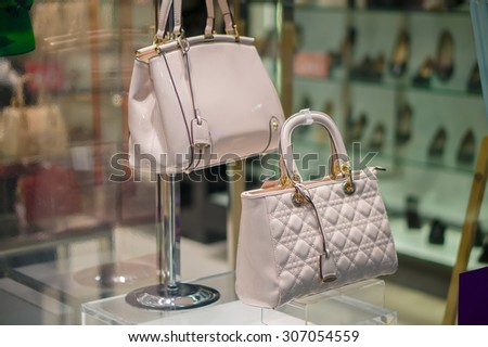 Woman luxury leather bag on table in store - stock photo