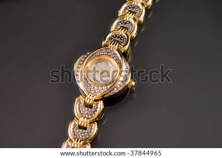 Woman luxury watch in gold tone with crystals on black background. - stock photo