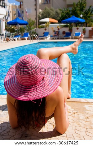 Woman lying and relaxing by a large swimming pool on holiday