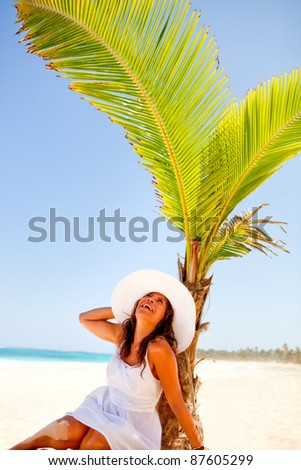 Woman lying at the beach under a palm tree - stock photo