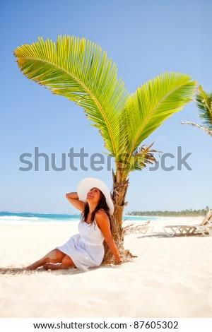 Woman lying at the beach under a palm tree avoiding the sun - stock photo