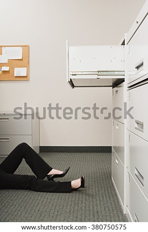 Woman lying by filing cabinet - stock photo