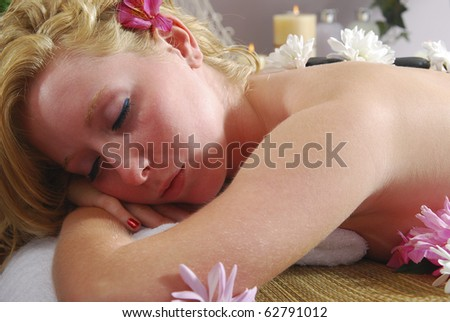 Woman lying down for hot stone treatment at spa - stock photo