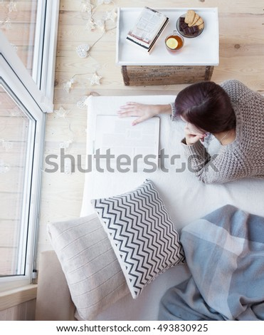 Woman lying down home on living room couch relaxing and reading magazine. Christmas lights on the floor, books and sweets on the table