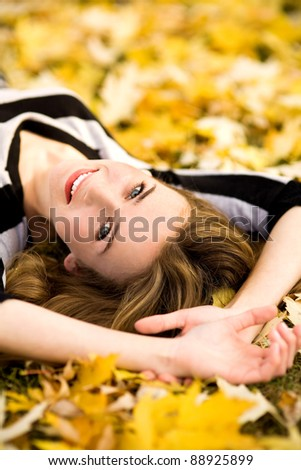 Woman lying down in autumn leaves - stock photo