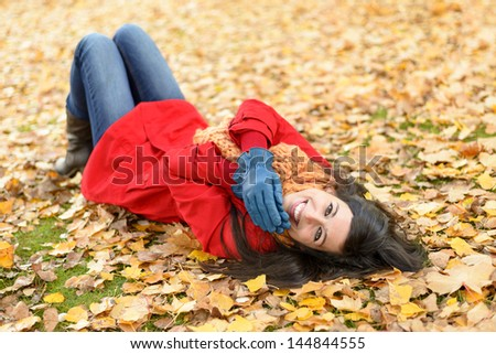 Woman lying down on autumn golden leaves and smiling. Positive happy brunette in red coat  enjoying on fall season. Caucasian girl looking at camera. - stock photo
