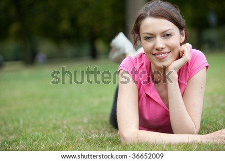 Woman lying down outdoors on the grass - stock photo