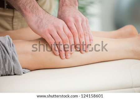 Woman lying forward while a man massaging her calf indoors - stock photo