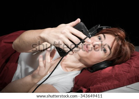 Woman lying in a bed in headphones looking to the player.