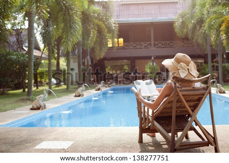 Woman lying in a deck-chair in a hotel and enjoying a book reading - stock photo