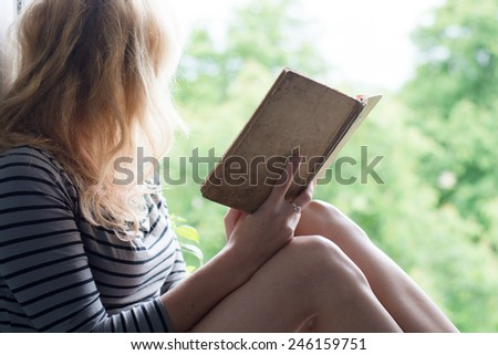 Woman lying in a garden and enjoying book reading