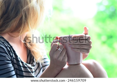 Woman lying in a garden and enjoying cup of tea or coffee - stock photo