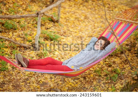 Woman lying in a hammock in the forest - stock photo