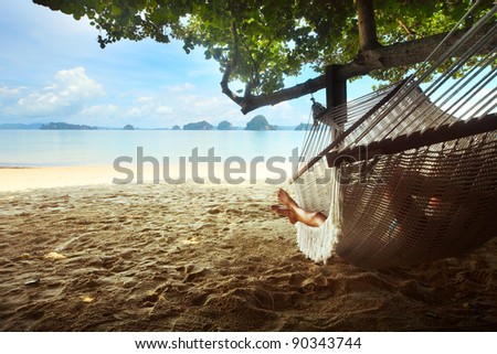Woman lying in a hammock in tree's shadow on a beach - stock photo