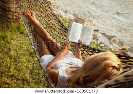 Woman lying in a hammock on the beach and enjoying a book reading - stock photo