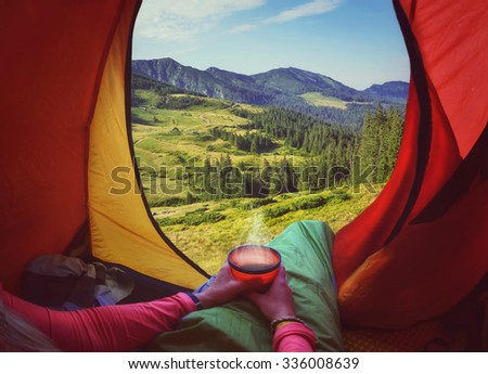 Woman lying in a tent with coffee ,view of mountains and sky   - stock photo