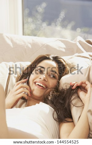 Woman lying in bed and talking on cell phone