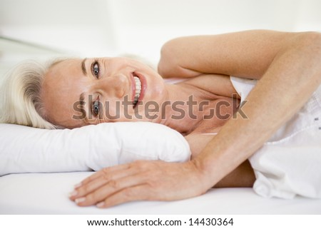 Woman lying in bed smiling - stock photo
