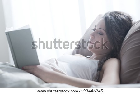 Woman lying in bed while reading a book  - stock photo