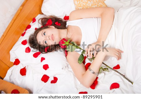 Woman lying in bed with a rose - stock photo